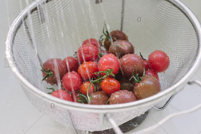 Tomatoes being rinsed in a colander