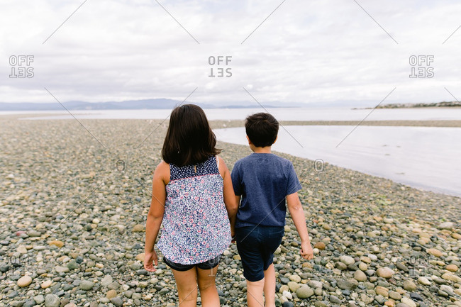 Two children walking together along a rocky beach