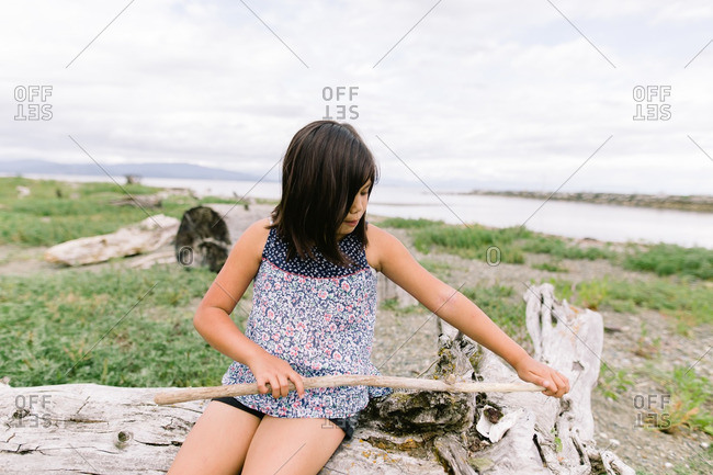 Girl sitting outside playing with driftwood along a riverbank