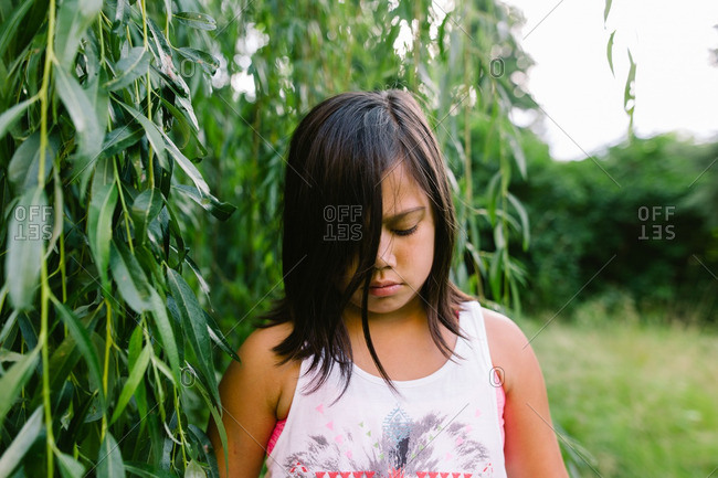 Girl standing next to a tree looking down at the ground