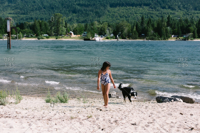 Girl standing on a lakeshore with her dog