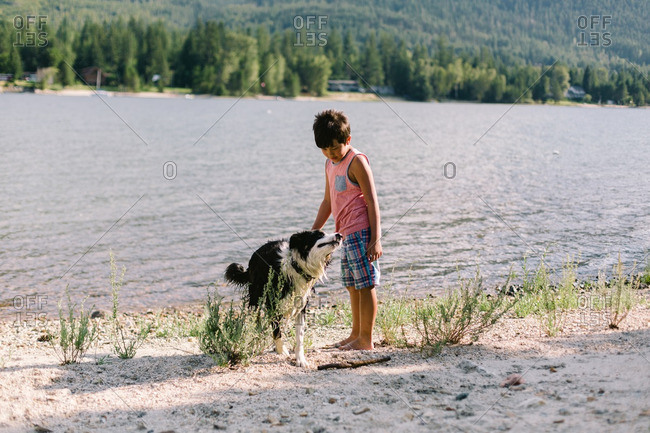 Boy standing on a lakeshore with his dog