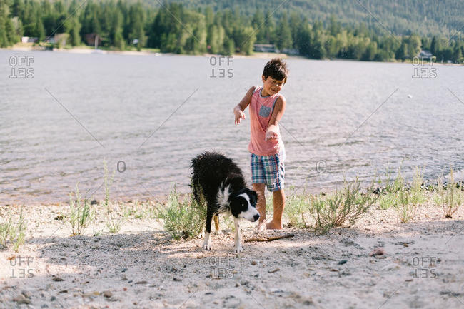 Boy standing on a lakeshore with his wet dog