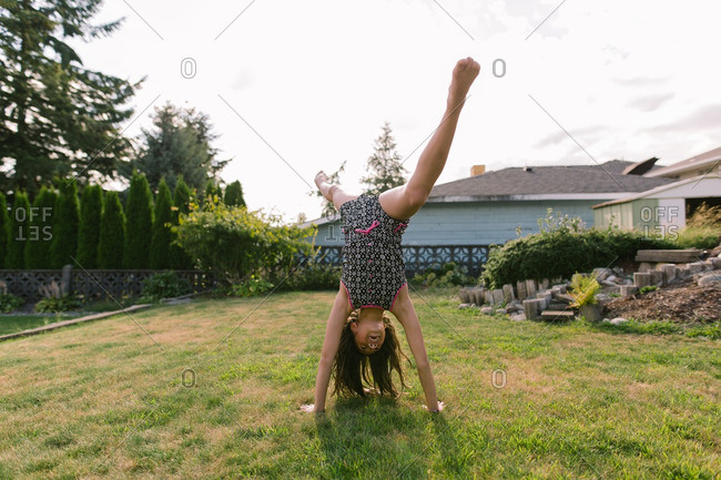 Portrait of a girl doing a cartwheel outside