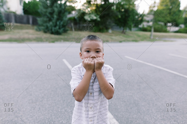 Boy holding his hands to his mouth