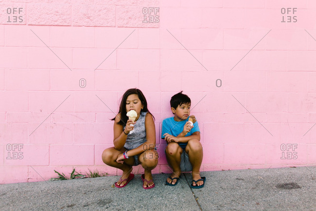 Two children sitting against a wall eating ice cream