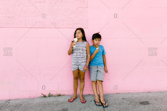 Two children standing against a wall eating ice cream