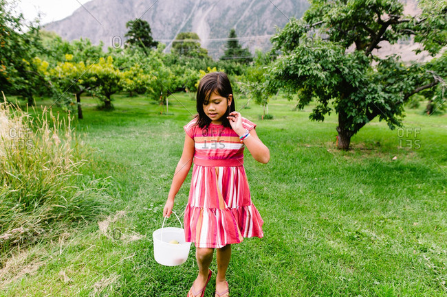 Girl walking through a fruit orchard holding a bucket