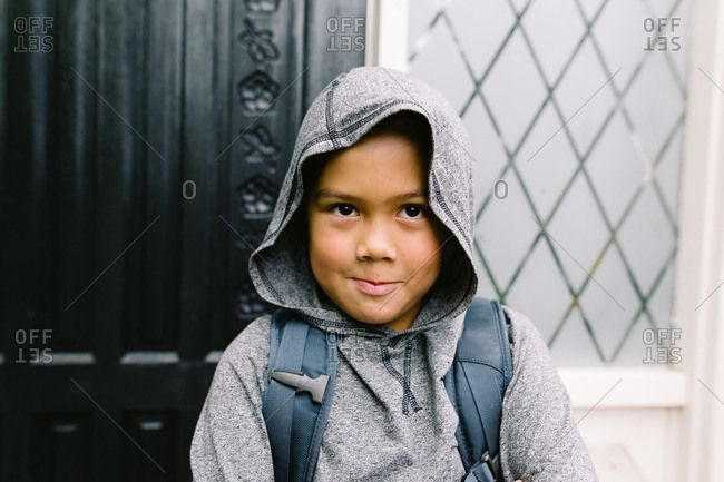 Boy wearing a hooded sweatshirt and a backpack standing near a door
