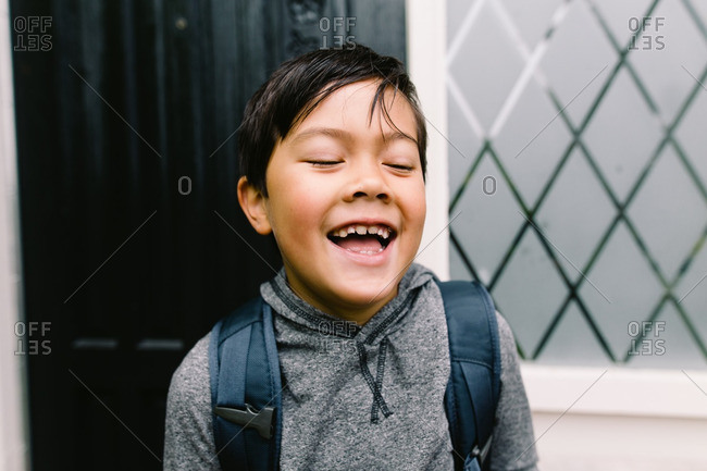Boy wearing a hooded sweatshirt and a backpack laughing