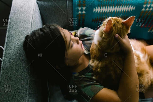Girl lying down on a couch holding a cat