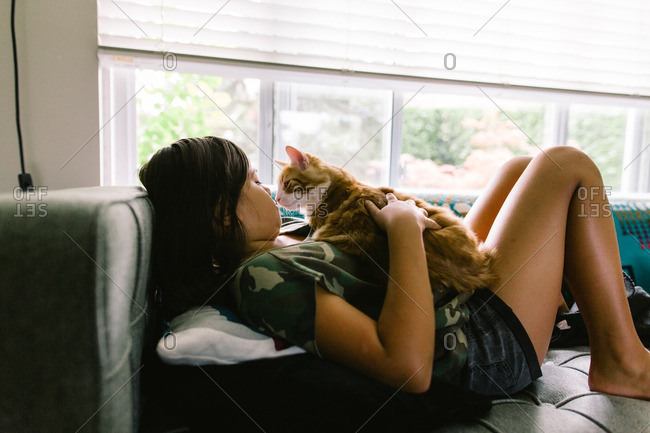 Girl lying down on a couch holding her pet cat