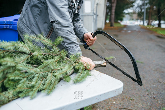 Man sawing the end off of a Christmas tree