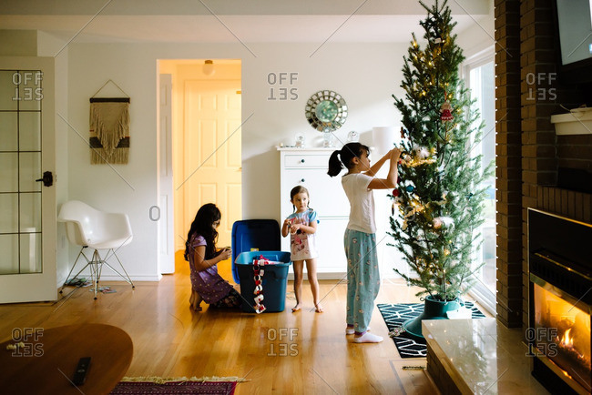 Three girls decorating a Christmas tree in front of a bright window