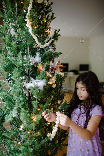 Girl decorating a Christmas tree with popcorn and ornaments