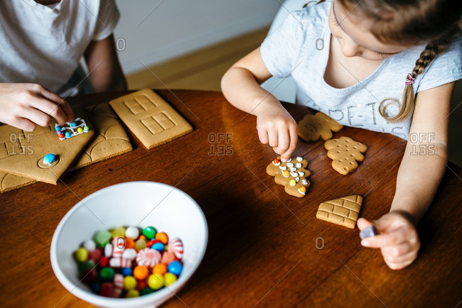 Two sisters decorating a gingerbread house