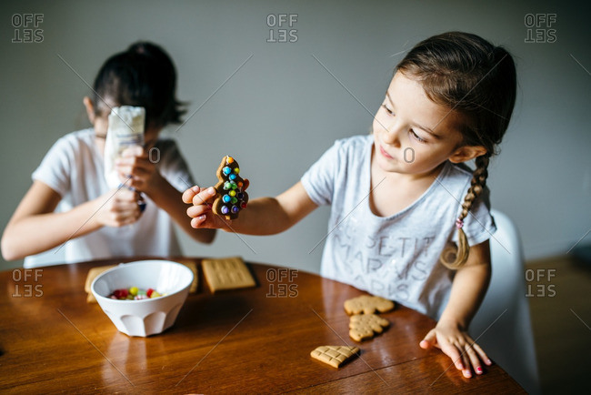 Sisters decorating pieces of a gingerbread house