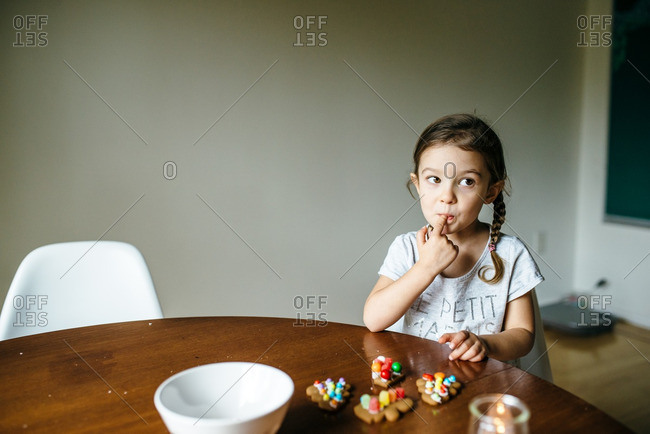Little girl with decorated gingerbread licking her finger