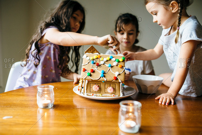 Three sisters adding candy to an assembled gingerbread house