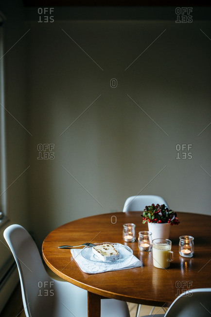 Slice of cake and eggnog on a kitchen table with Christmas decorations