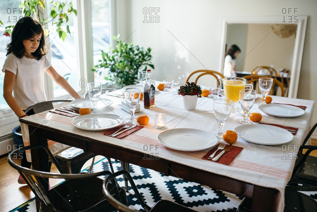 Girl at a dining table set for Christmas breakfast