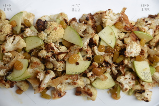 Platter of roasted cauliflower with apples and golden raisins