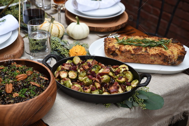 Platters of food on a rustic table with autumn vegetables and greenery