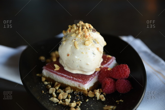 Layered raspberry dessert with ice cream, nuts and fresh berries