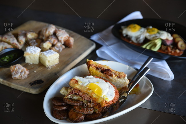 Various platters of breakfast dishes with pastries, a sandwich and eggs
