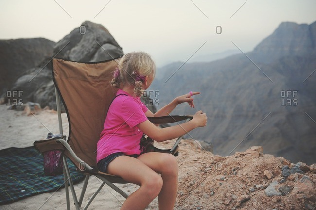 Girl sitting in mountains, UAE