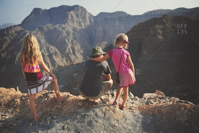 Man and girls in rugged mountains