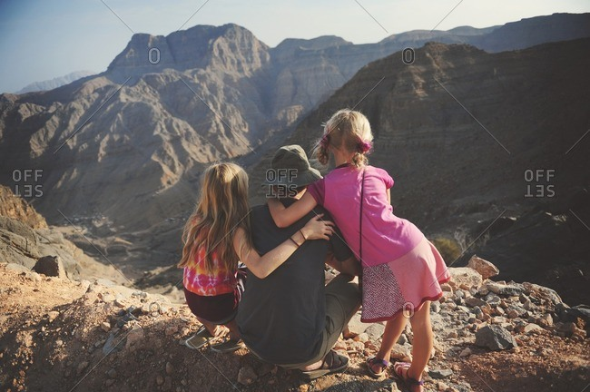 Man and girls over rugged mountains