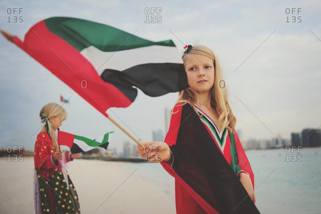 Girls waving UAE flags on beach