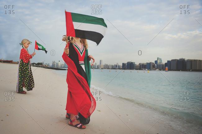 Girls holding UAE flags on beach