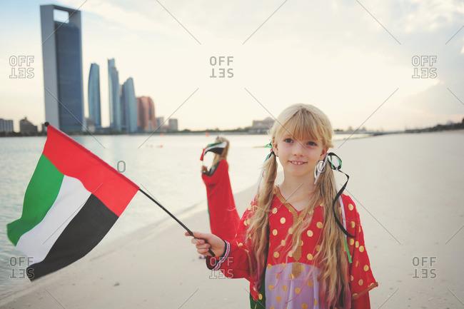 Girls on beach holding UAE flags