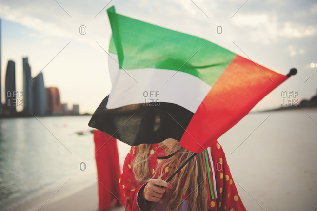 Girl covering face with UAE flag