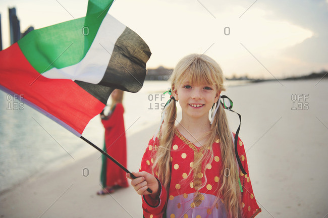 Girls on beach with UAE flags