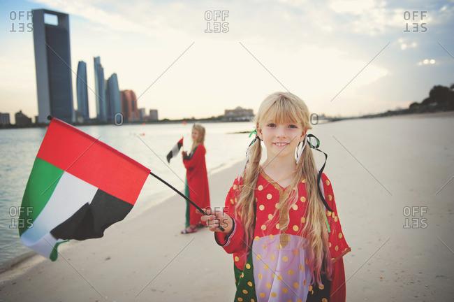 Girls on beach waving UAE flags