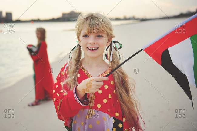 Girls on a beach with UAE flags