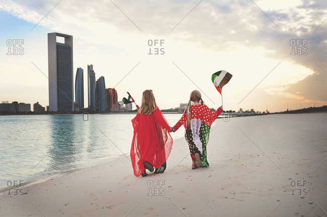 Girl walking beach with UAE flags