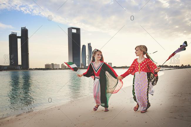 Girl walking beach waving UAE flags