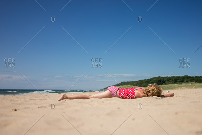 Girl lying down on sandy beach