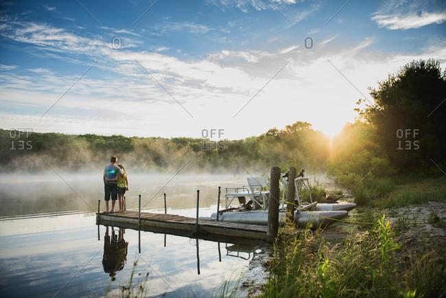 Kids on lake dock at sunset