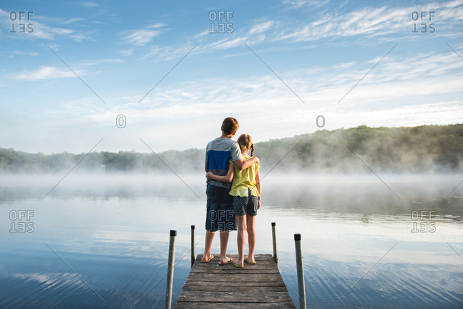Kids on dock by misty lake