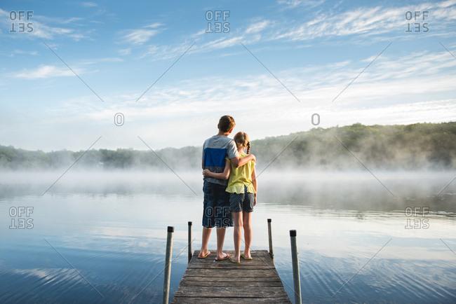 Kids on dock by misty lake