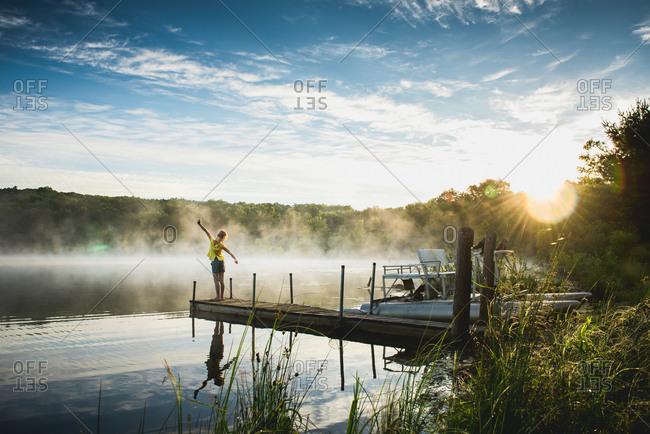 Girl stretching on lake dock