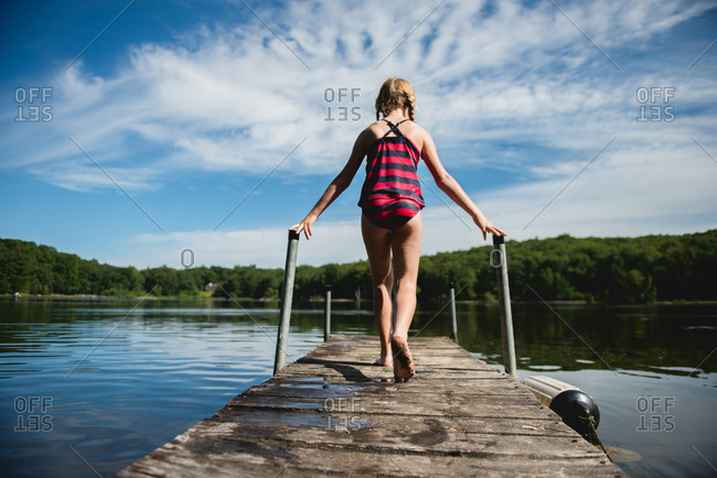 Girl running on a lake dock