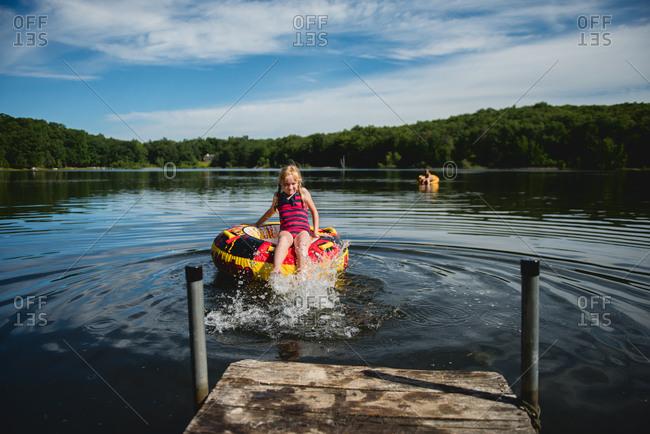 Girl kicking on raft on lake