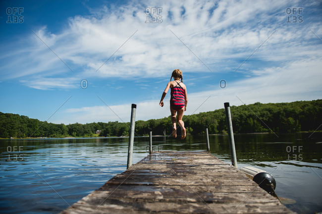 Girl leaping from a lake dock