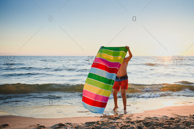 Boy setting his towel on beach